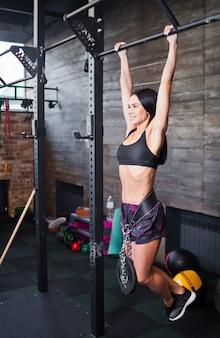 Młoda brunetka kobieta wisi na drążku z obciążeniem na pasku w siłowni