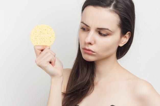 Młoda brunetka kobieta z gąbkami do oczyszczania skóry w dłoniach