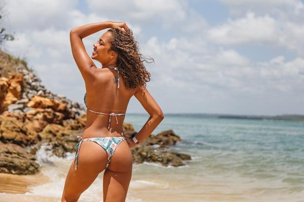Młoda brunetka kobieta z kolorowym bikini latem na plaży
