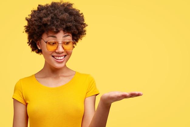 Młoda brunetka kobieta z kręconymi włosami i modnymi okularami