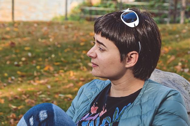 Młoda brunetka kobieta z krótkimi włosami w zamyśleniu wygląda z boku na tle jesiennych liści
