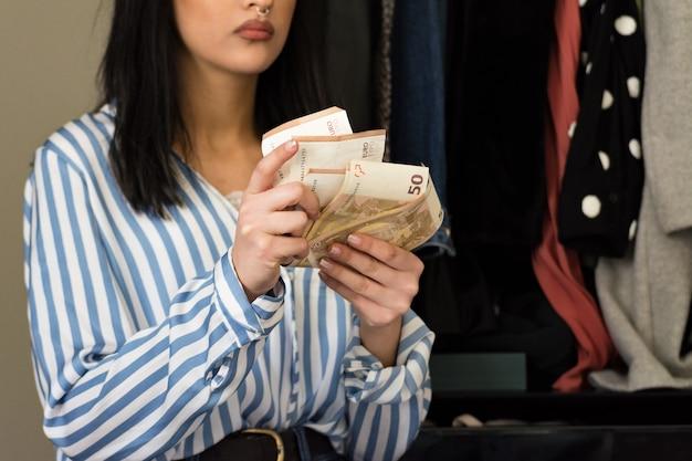 Młoda brunetka kobieta z makijażem patrząc na ubrania w swojej szafie i zastanawiając się, które ubrania kupić. liczenie zaoszczędzonych pieniędzy. koncepcja butów i moda damska.