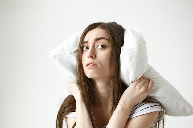 Młoda brunetka kobieta z niechlujną fryzurą obejmującą uszy przy użyciu białej poduszki, patrząc w bok z frustracją