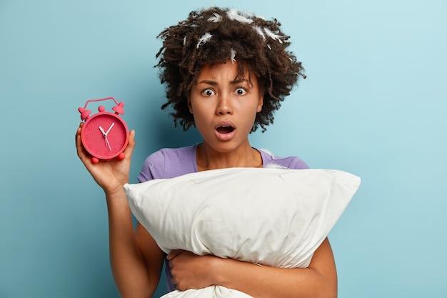 Młoda brunetka kobieta z piórami we włosach, trzymając poduszkę i budzik