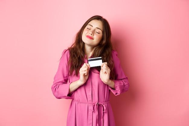 Młoda brunetka kobieta z zachwytem przytula swoją kartę kredytową, uśmiechając się zadowolony, stojąc przed różową ścianą.