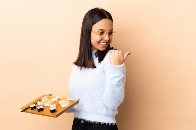 Młoda brunetka kobiety rasy mieszanej gospodarstwa sushi na pojedyncze ściany, wskazując na bok, aby przedstawić produkt