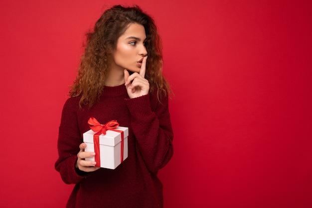 Młoda brunetka kręcone kobieta na białym tle na czerwonym tle ściany