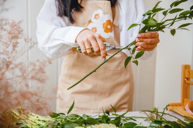 Młoda brunetka kwiaciarka w fartuchu odcina liście z łodyg, zanim zacznie tworzyć bukiet w swoim warsztacie