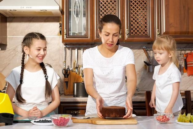 Młoda brunetka mama piecze tort urodzinowy z dwiema córeczkami w kuchni, wyciąga biszkopt z foremki. gotowanie rodzinne.