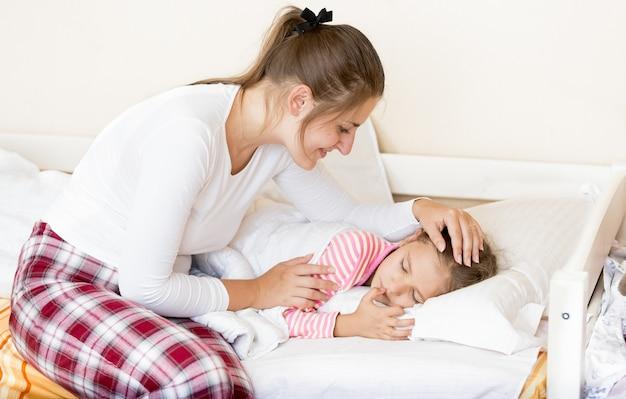 Młoda brunetka matka budzi śpiącą córkę rano