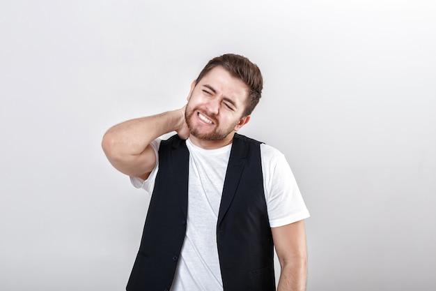 Młoda brunetka mężczyzna w białej koszuli z bólem szyi na szarym tle.
