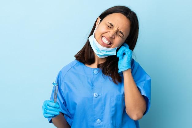 Młoda brunetka mieszająca biegowa dentysta kobiety mienia narzędzia nad odosobnionym tłem udaremniającym i zakrywającymi ucho