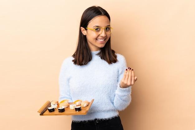 Młoda brunetka mieszanej rasy kobieta trzyma sushi nad ścianą zaprasza przyjść z ręką. cieszę się, że przyszedłeś