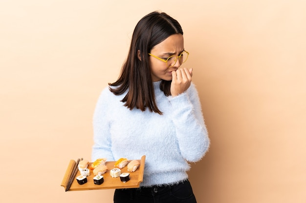 Młoda brunetka mieszanej rasy kobieta trzymająca sushi na białym tle, mająca wątpliwości