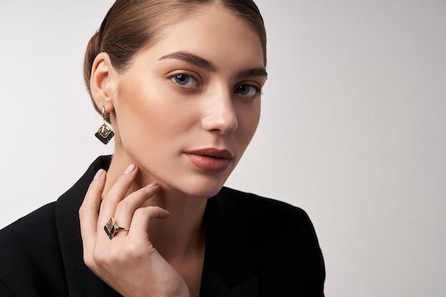 Młoda brunetka model demonstrujący biżuterię