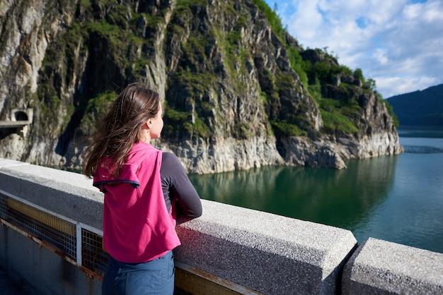 Młoda brunetka, patrząc daleko w dal, podziwiając piękno zielonych trawiastych skał i jeziora vidraru w rumunii