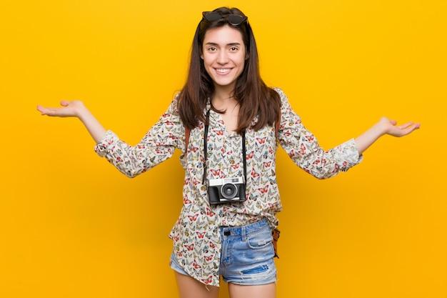 Młoda brunetka podróżniczka sprawia, że skala z rękami, czuje się szczęśliwa i pewna siebie.