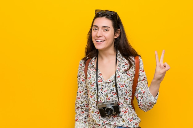 Młoda brunetka podróżnika kobieta pokazuje zwycięstwo znaka i ono uśmiecha się szeroko.