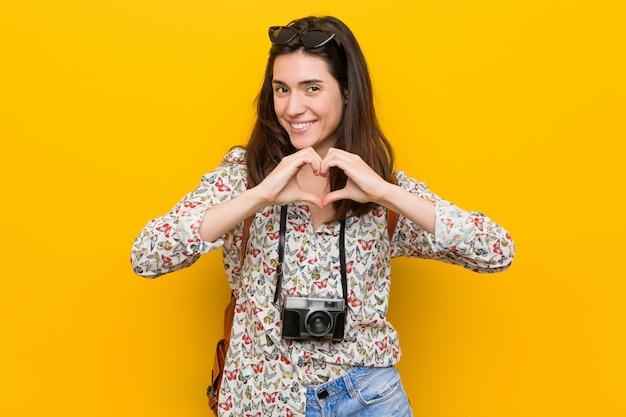 Młoda brunetka podróżnika kobieta uśmiecha się kierowego kształt i pokazuje z rękami.
