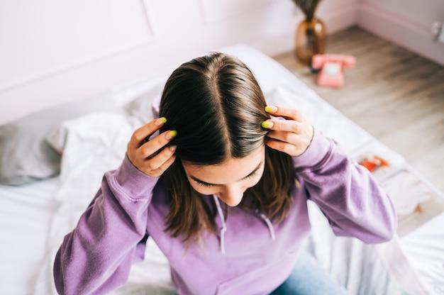 Młoda brunetka pokazuje jej skórę głowy, cebulki włosów, kolor, siwe włosy, wypadanie włosów lub problem z suchą skórą głowy.