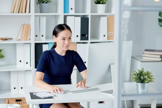 Młoda brunetka projektant lub kierownik biura patrząc na ekran komputera