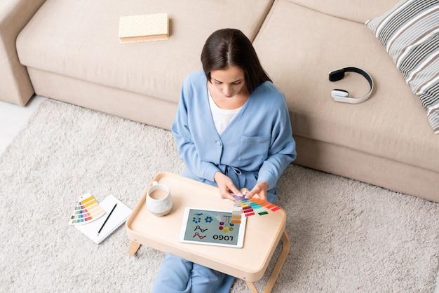 Młoda brunetka projektantka w niebieskiej piżamie siedzi na podłodze przy kanapie i wybiera kolory z palety dla nowego logo na wyświetlaczu tabletu