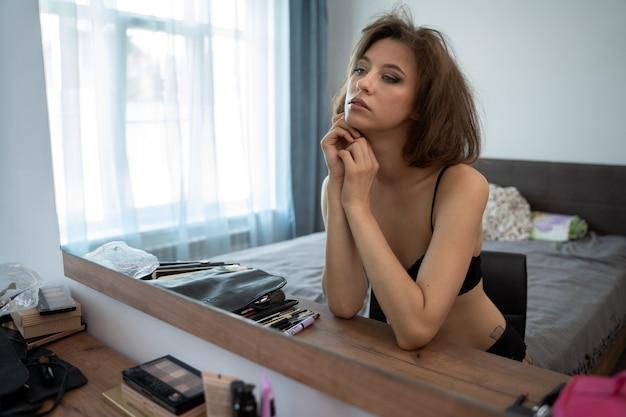 Młoda brunetka rano siedzi w swojej sypialni przed lustrem właśnie się obudziła