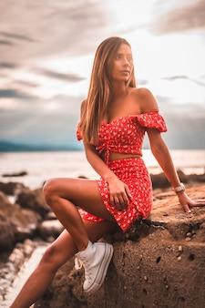 Młoda brunetka rasy białej kobiety w czerwonej sukience na plaży itzurrun w miejscowości zumaia, gipuzkoa. kraj basków. sesja lifestylowa na szczycie skały nad morzem