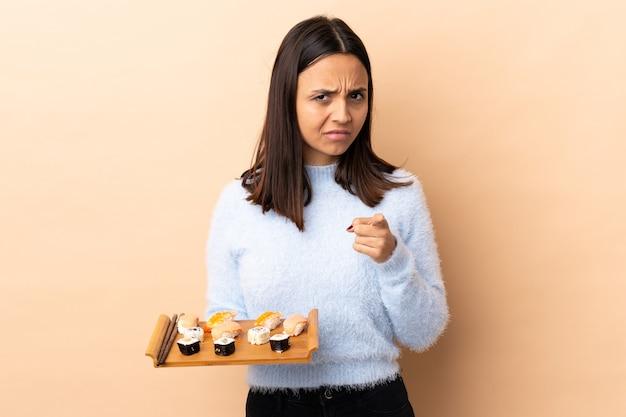 Młoda brunetka rasy mieszanej kobieta sfrustrowana trzymając sushi na odizolowanej ścianie i wskazując do przodu