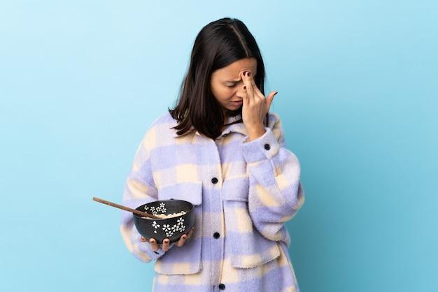 Młoda brunetka rasy mieszanej kobieta trzyma miskę pełną makaronu nad izolowaną niebieską ścianą z bólem głowy.