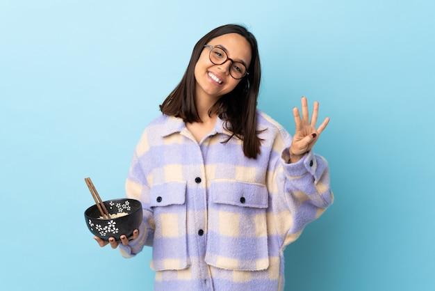 Młoda brunetka rasy mieszanej kobieta trzyma miskę pełną makaronu nad odizolowaną niebieską ścianą szczęśliwa i liczy cztery palcami.