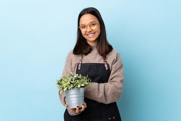 Młoda brunetka rasy mieszanej kobieta trzyma roślinę na odosobnionym niebieskim śmiechem.