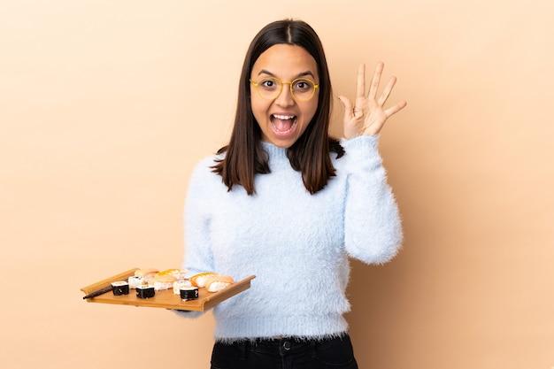 Młoda brunetka rasy mieszanej kobieta trzyma sushi na odizolowanej ścianie licząc pięć palcami