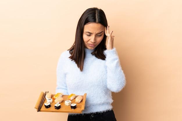 Młoda brunetka rasy mieszanej kobieta trzyma sushi na odizolowanej ścianie z bólem głowy