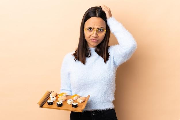 Młoda brunetka rasy mieszanej kobieta trzyma sushi z wyrazem frustracji i niezrozumienia