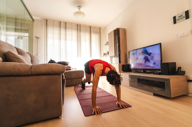 Młoda brunetka robi ćwiczenia w domu w kwarantannie covid19, robi pompki zgodnie z instrukcjami w telewizji
