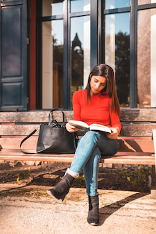 Młoda brunetka siedzi na ławce w parku, czytając książkę
