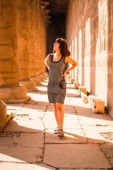 Młoda brunetka spacerująca po kolumnach świątyni edfu w pobliżu miasta asuan. egipt