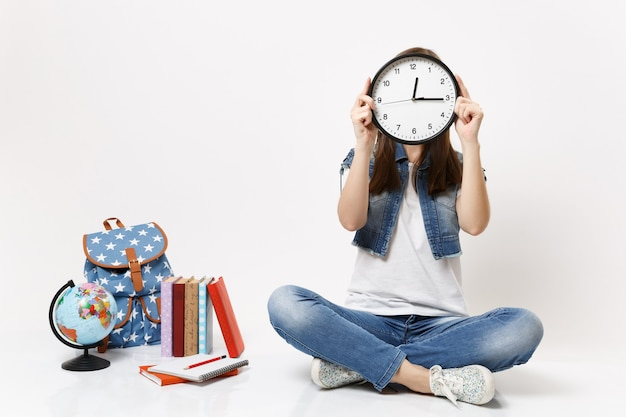 Młoda brunetka studentka w dżinsowych ubraniach zakrywających twarz z budzikiem, siedząca w pobliżu globu plecaka szkolne książki na białym tle