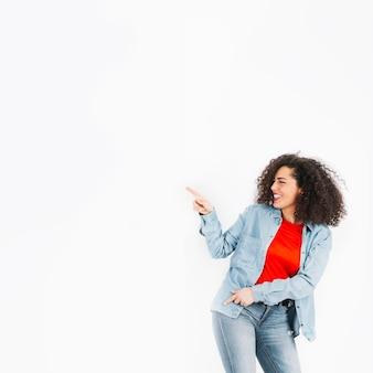Młoda brunetka tańczy i wskazując w lewo