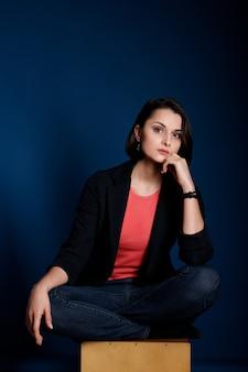 Młoda brunetka ubrana w koralową koszulkę bez rękawów, czarną marynarkę i niebieskie dżinsy na ciemnoniebieskim tle