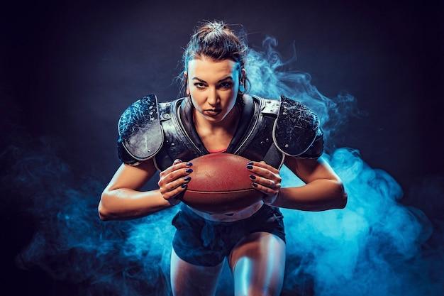 Młoda brunetka ubrana w mundur rugby grający na pozycji napastnika z piłką.