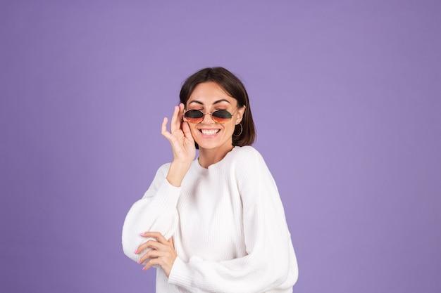 Młoda brunetka w biały sweter dorywczo na białym tle na fioletowej ścianie