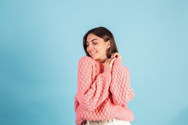 Młoda brunetka w ciepły różowy sweter na białym tle na niebieskiej ścianie