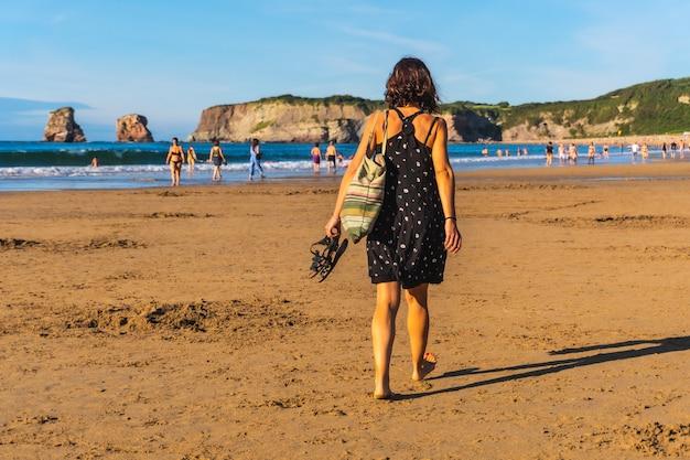 Młoda brunetka w czarnej sukience i okularach przeciwsłonecznych spacerująca po plaży w hendaye we francuskim kraju basków. francja. spacerując w letnie popołudnie, styl życia