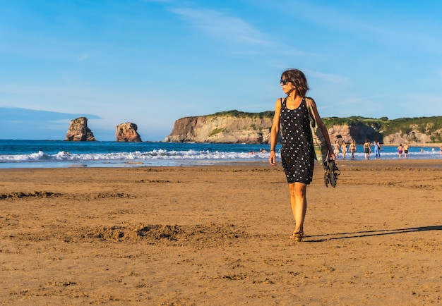 Młoda brunetka w czarnej sukience i okularach przeciwsłonecznych spacerująca po plaży w hendaye we francuskim kraju basków. francja. spacerując w letnie popołudnie