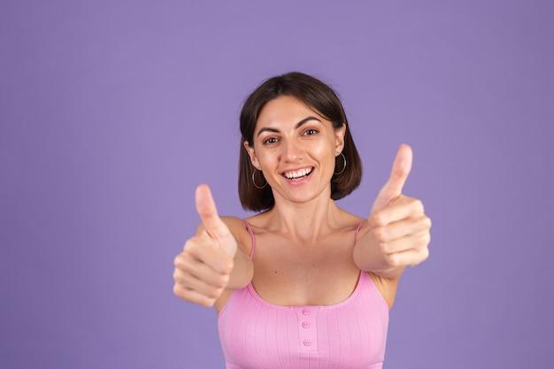 Młoda brunetka w górę na białym tle na fioletowej ścianie