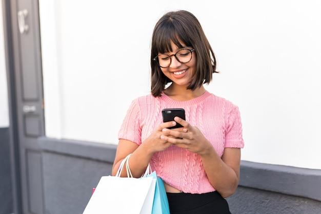 Młoda brunetka w mieście trzyma torby na zakupy i pisze wiadomość telefonem komórkowym do przyjaciela
