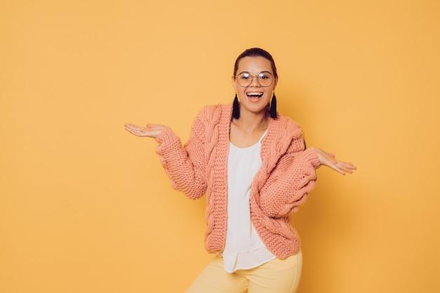 Młoda brunetka w okularach ubrana w różowy sweter z dzianiny w białą bluzkę i żółte spodnie, z radosnym zaskoczeniem rozkłada ręce, uśmiechając się szeroko, na żółtym tle. koncepcja zakupów i stylu życia.