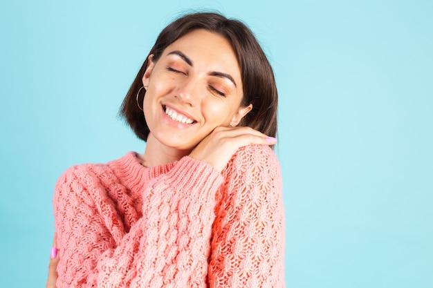 Młoda brunetka w różowym swetrze na białym tle na niebieskiej ścianie